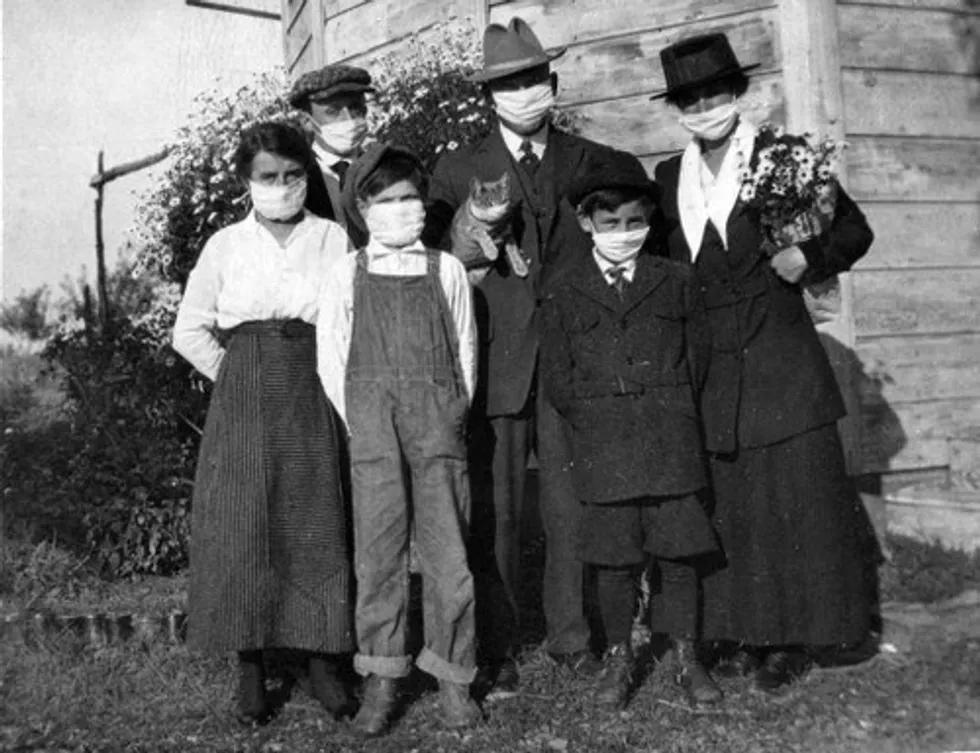 Photo noir et blanc d'une famille de 6 personnes, toutes portant un masque blanc recouvrant leur nez et leur bouche