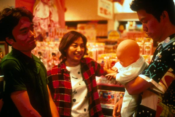 un homme et une femme regarde un homme tennant un poupon dans un magazin